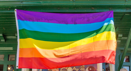 transsexual: A Gay Pride Flag flying in Storefront Stock Photo
