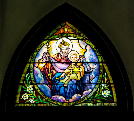 Arched stain glass window in church on black background Stock Photo