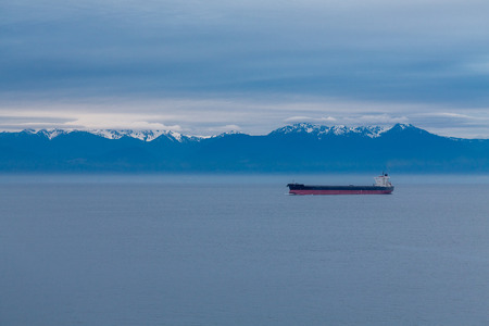 freighter: A freighter on a calm sea at dawn with snow capped mountains in the background Stock Photo