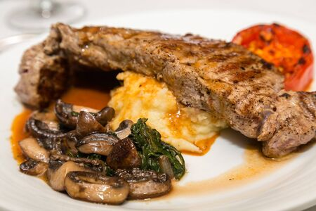 new york strip: New York strip steak on plate with mushrooms and potatoes Stock Photo