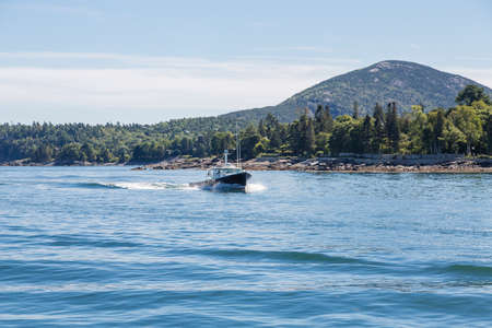 A black fishing boat cutting through blue Maine water