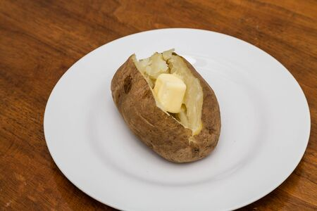 russet potato: Hot baked potato on white plate with butter