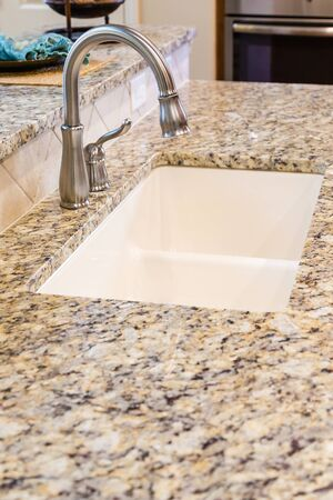 countertops: Modern Stainless Steel Faucet on Granite Kitchen Counter in New Home