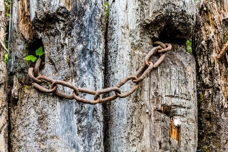 rusty chain: Old rusty chain on a weathered wooden post Stock Photo