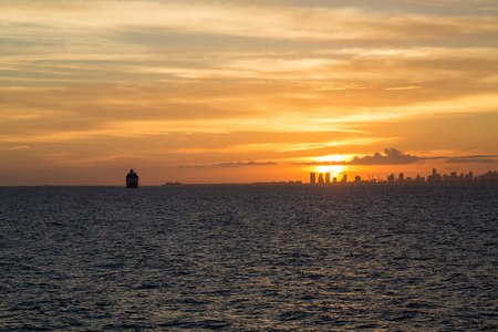 freighter: Miami skyline at sunset from the sea with freighter on the horizon