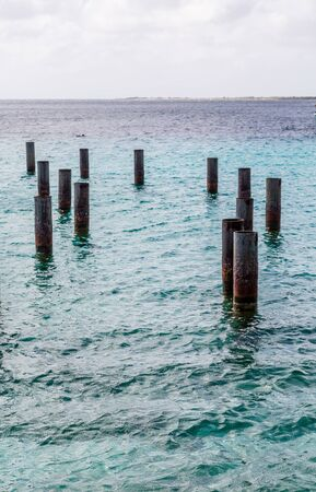 pilings: Rusty Metal Pilings in blue water of Harbor