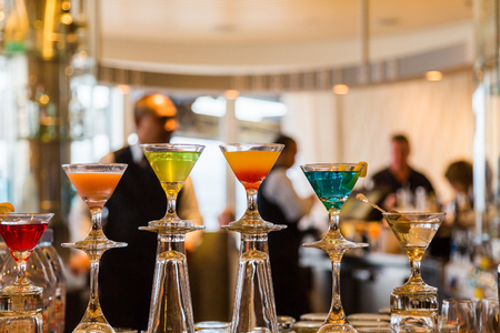 bartenders: Colorful Cocktails in a Bar with Bartenders and Patrons in Background Stock Photo