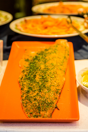 Salmon fillet on display at a deli with seasoning and spices