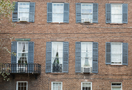 red shutters: Black shutters on an old red brick building Stock Photo