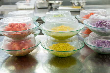 prep: Cut vegetables under serving domes in commercial kitchen Stock Photo