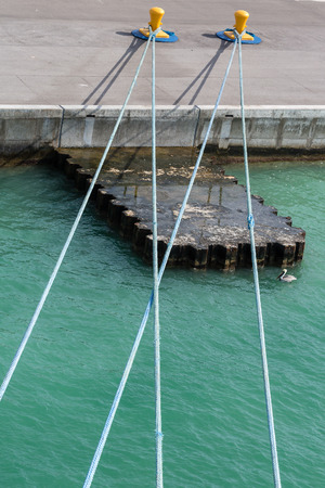 bollards: Blue ropes to yellow bollards on a concrete pier