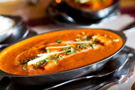 serving dish: Spicy Indian Food in a serving dish on a table