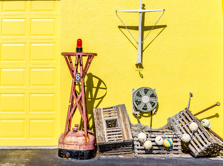 Old Lobster Traps by Yellow Wall in Coastal Village
