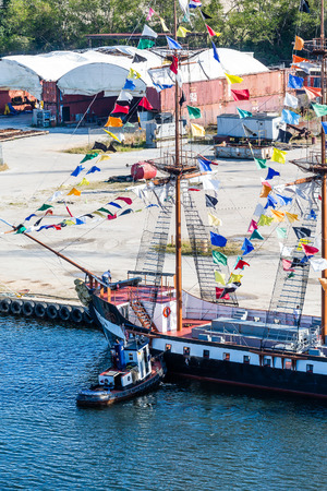 Tugboat docking a three masted party boat with colorful pennants