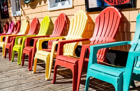 Orange And Yellow Adirondack Chairs On Sidewalk Stock Photo   65629800