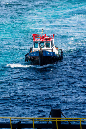 A red white and blue pilot boat in the blue water off Curacao