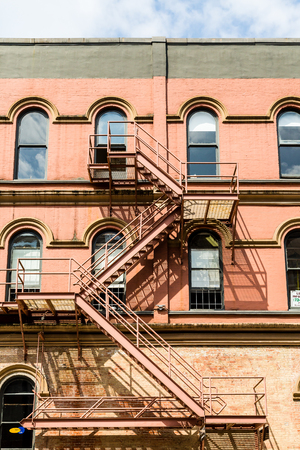 fire brick: An old red rusty fire escape down a brick building Stock Photo