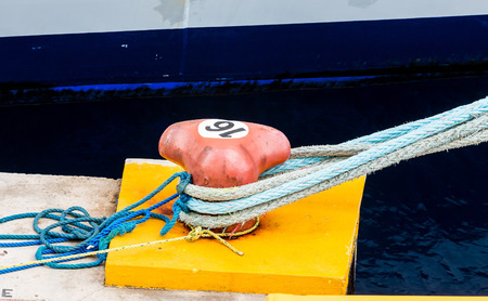 Blue Ropes on a Red Bollard in a Harbor Stock Photo