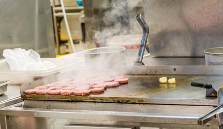 Hamburguesas fumadores en la plancha de cocina comercial Foto de archivo - 65634242