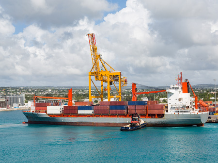 Freighter with Crane and Tugboat in Barbados Stock Photo