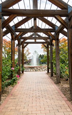 wood rose: Wood rose trellis over brick walkway in garden Stock Photo
