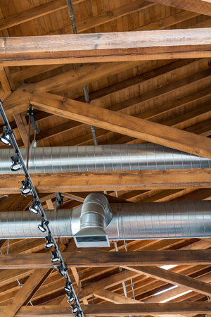 rafters: Ductwork and lights below a natural wood roof and rafters Stock Photo