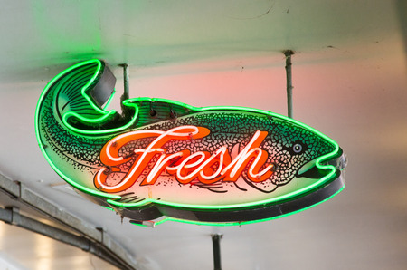 Neon Fresh Fish Sign hanging from ceiling