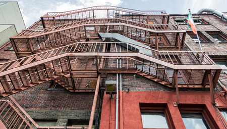 Red Metal Fire Escapes up a brick building Stock Photo