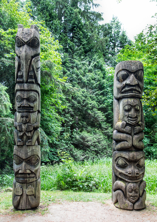 Two Old Totem Poles in Forest in Alaska