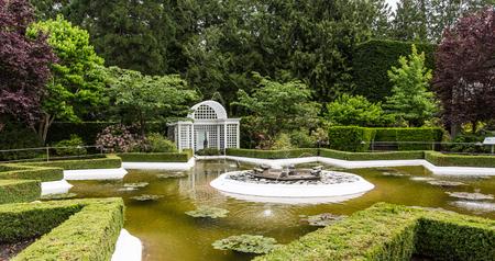 Gebeeldhouwde fontein in openbare tuin met gazebo Stockfoto