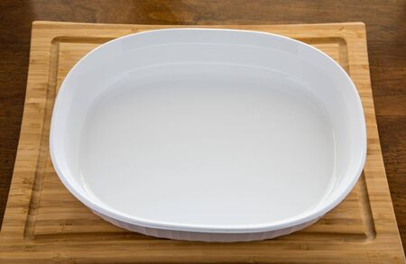 Empty White Casserole Dish on Wood Cutting Board and Table