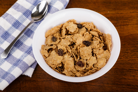 A bowl of wheat bran cereal with raisin