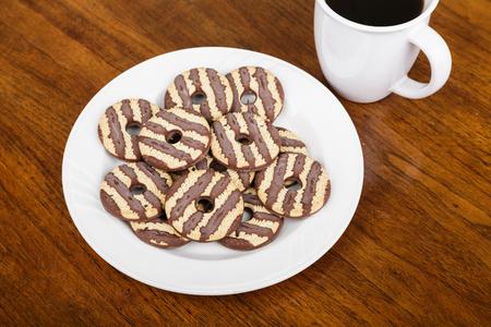Fudge gestreepte koekjes op plaat met koffie op houten tafel Stockfoto