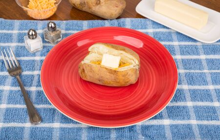 Baked Potato on Red Plate with Cheese and Butter