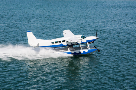 Blue and White Seaplane Taking Off in Aqua Water Foto de archivo