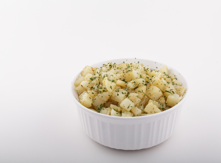 A white casserole dish full of cooked potatoes garnished with parsley Stock fotó