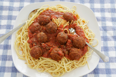 Spaghetti and Meatballs with Tomato Sauce on Square Plate with fork Фото со стока