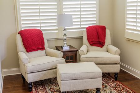 White Chairs with Red Throws in Sun Room Stockfoto