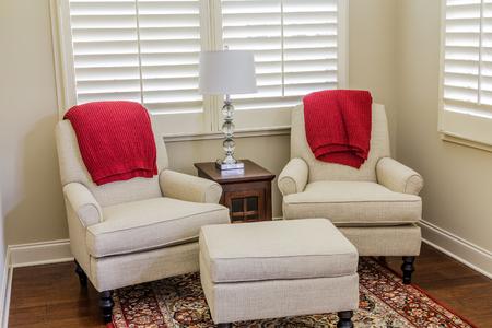 Witte stoelen met rode worpen in de serre Stockfoto