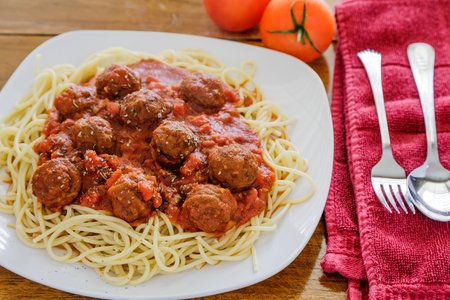 Spaghetti and Meatballs on a Square Plate with Tomatoes, fork and knife