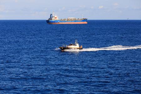 Pilot Boat Past Tanker on Blue Sea