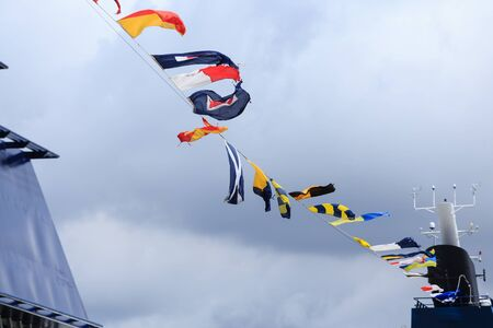 Nautical Flags Under Clouds and Wind