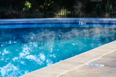 Steam Rising from Heated Swimming Pool with Concrete Deck Stock Photo
