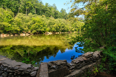 Old Mill Foundation in River through Forest Imagens