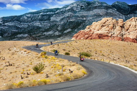 Motorcyclists riding a road into the dessert mountains Stock Photo