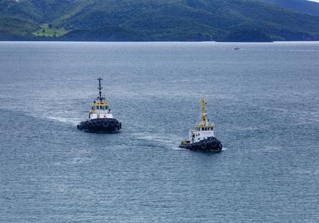 Two tugboats crossing a calm blue bay Foto de archivo
