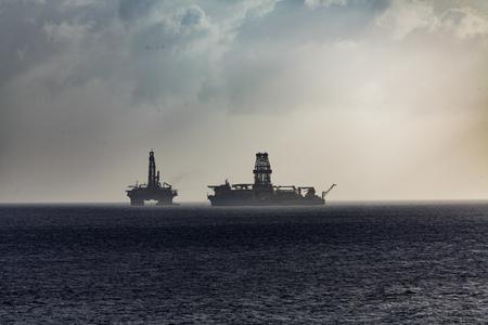 Floating Oil Rigs on Ocean in Sillhouette