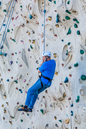 Middle Aged Man on Climbing Wall