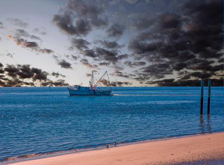 Barco camaronero y postes en la playa Foto de archivo