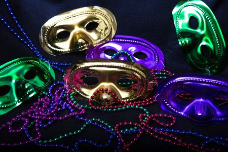 Purple, Green and Gold Mardi Gras masks with beads on a black background